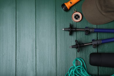 Flat lay composition with trekking poles and other hiking equipment on green wooden background, space for text