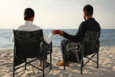 Couple sitting in camping chairs and clinking mugs on beach, back view