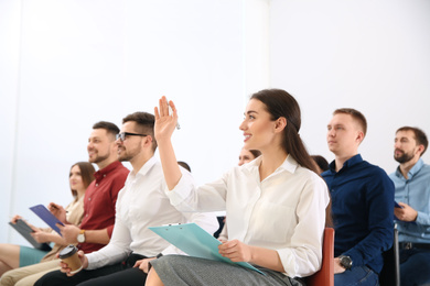 Young woman raising hand to ask question at business training indoors