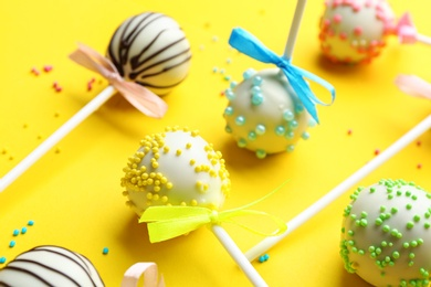 Different tasty cake pops with sprinkles on yellow background