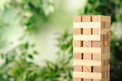 Jenga tower made of wooden blocks outdoors. Space for text