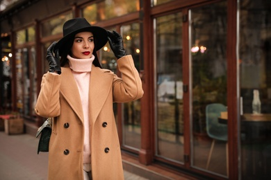 Young woman wearing stylish clothes on city street, space for text. Autumn look
