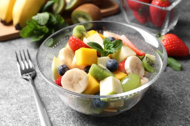 Delicious fresh fruit salad in bowl on grey table