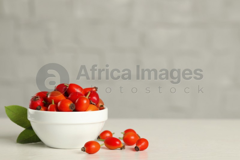 Ripe rose hip berries with green leaves on white wooden table. Space for text
