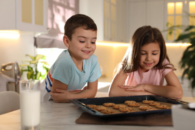 Cute little children with cookies and milk in kitchen. Cooking pastry