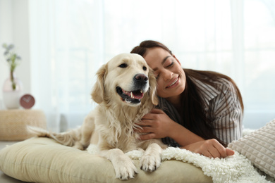 Young woman and her Golden Retriever at home. Adorable pet