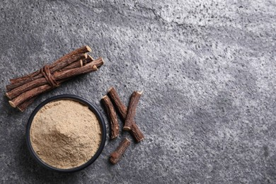 Powder in bowl and dried sticks of liquorice root on grey table, flat lay. Space for text