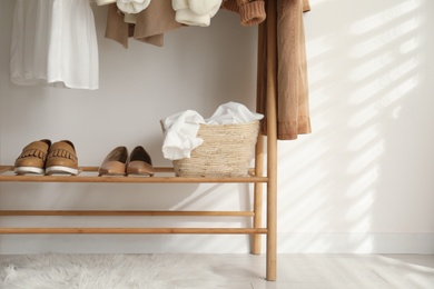 Rack with stylish shoes and women's clothes indoors. Modern interior design