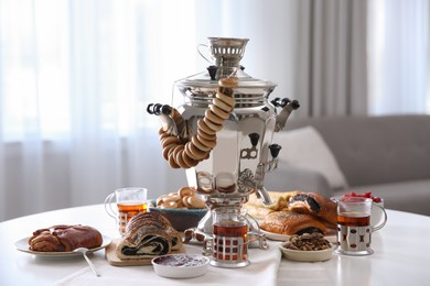 Traditional Russian samovar with treats on white table at home