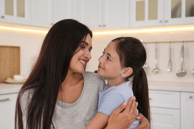 Happy mother and daughter hugging in kitchen. Single parenting