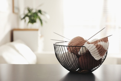 Yarn balls and knitting needles in metal basket on grey table indoors, space for text. Creative hobby