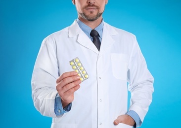 Professional pharmacist with pills on light blue background, closeup