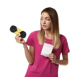 Confused young woman with disposable and reusable cloth menstrual pads on white background