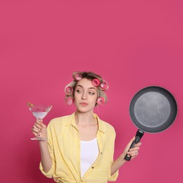 Young housewife with frying pan and glass of martini on pink background