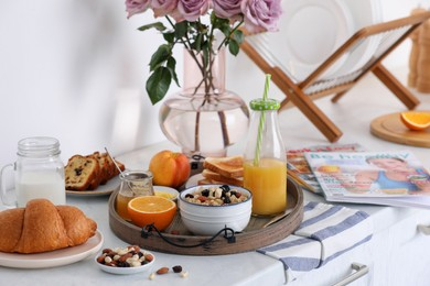 Tray with tasty breakfast on white table in morning