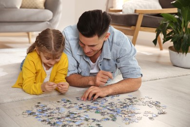 Happy father and his daughter playing with puzzles on floor at home