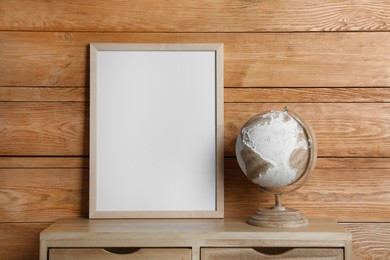 Empty frame with globe on table near wooden wall. Mockup for design