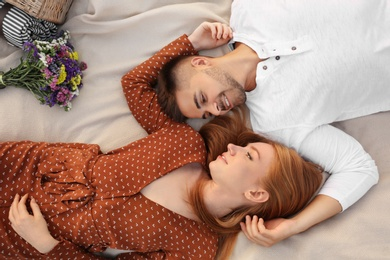 Happy young couple lying on picnic blanket, above view