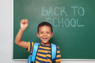 Little African-American child near chalkboard with text BACK TO SCHOOL