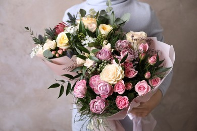 Woman with bouquets of beautiful flowers on beige background, closeup