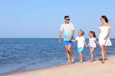 Happy family walking on sandy beach near sea, space for text. Summer holidays