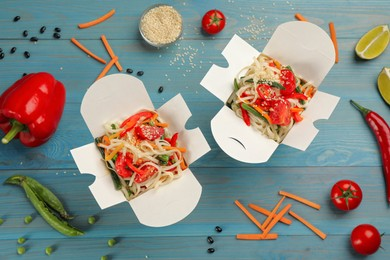 Boxes of vegetarian wok noodles with ingredients on light blue wooden table, flat lay