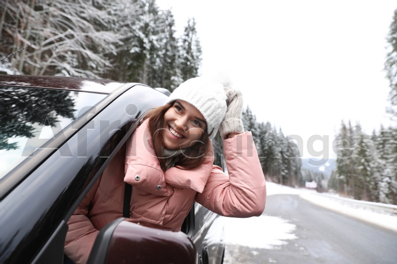 Young woman looking out of car window on road. Winter vacation