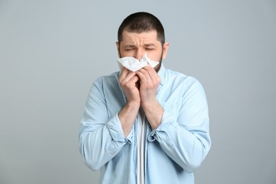 Man with tissue suffering from runny nose on light grey background