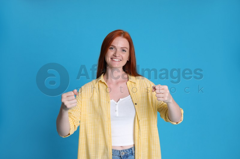 Happy young woman pretending to drive car on light blue background