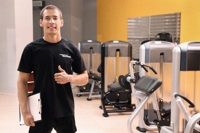 Portrait of personal trainer with clipboard in modern gym