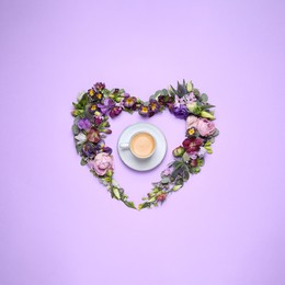 Beautiful heart made of different flowers and coffee on violet background, flat lay