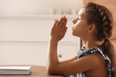 Cute little girl praying over Bible at table in room