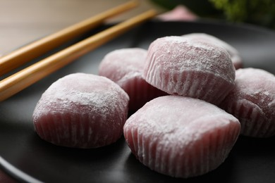 Delicious mochi and chopsticks on black plate, closeup. Traditional Japanese dessert