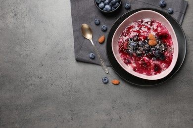 Tasty oatmeal porridge with toppings on grey table, flat lay. Space for text