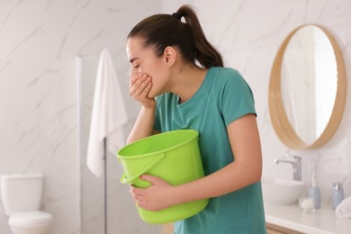 Young woman with bucket suffering from nausea in bathroom. Food poisoning