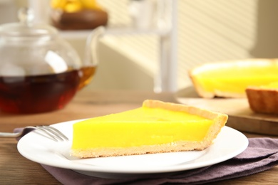 Slice of delicious homemade lemon pie on wooden table