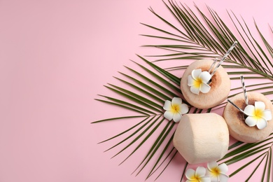 Fresh coconuts with drinking straws and flowers on pink background, flat lay. Space for text