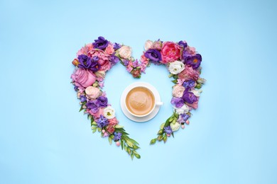 Beautiful heart shaped floral composition with cup of coffee on turquoise background, flat lay