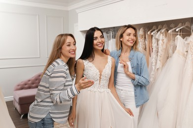 Bride with friends choosing wedding dress in boutique