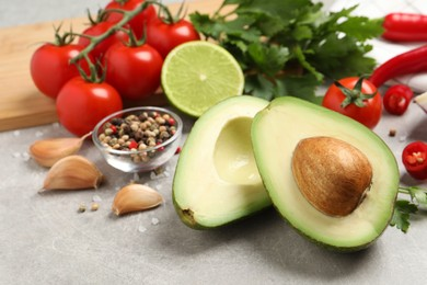 Fresh ingredients for guacamole on light grey table