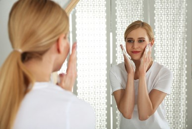 Happy young woman applying cleansing foam onto face near mirror in bathroom