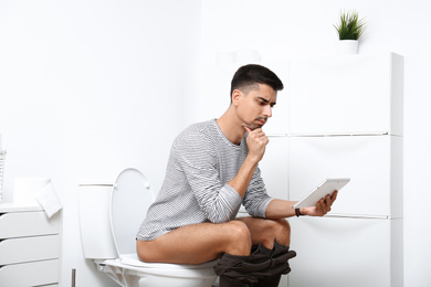 Man with tablet sitting on toilet bowl in bathroom