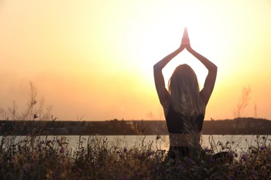 Young woman meditating near river at sunset, back view. Space for text