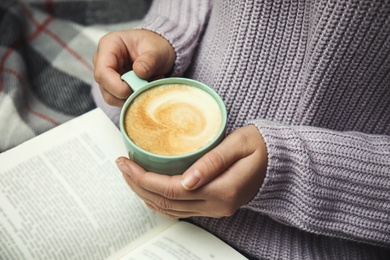 Woman with cup of coffee reading book at home, closeup