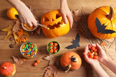 Women preparing Halloween pumpkin head jack lantern and holiday decorations on wooden table, flat lay composition