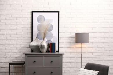 Stylish room interior with grey chest of drawers near white brick wall