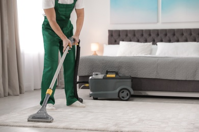 Professional janitor removing dirt from carpet with vacuum cleaner in bedroom, closeup. Space for text
