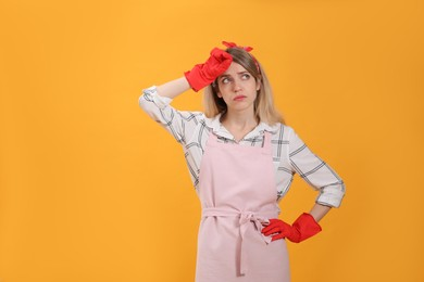 Young housewife in gloves on yellow background. Space for text