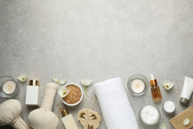 Flat lay spa composition with skin care products on grey table, space for text