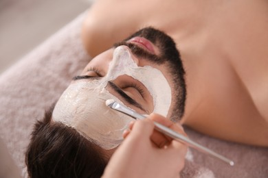 Cosmetologist applying mask on man's face in spa salon